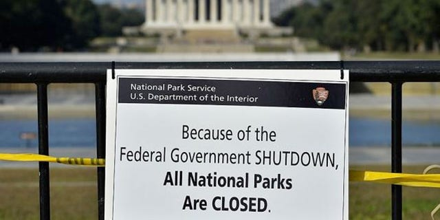 A National Park Service employee posted a sign on a barricade to close the Lincoln Memorial.