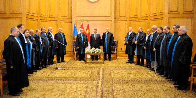 """In this image released by the Egyptian President, Egyptian President Mohammed Morsi, center left, stands with judges Farouk Sultan, second left, and Maher el-Beheri, center right, as he is sworn in at the Supreme Constitutional Court in Cairo, Egypt, Saturday, June 30, 2012. Islamist Mohammed Morsi promised a """"new Egypt"""" and unwavering support to the powerful military as he took the oath of office Saturday to become the country's first freely elected president, succeeding Hosni Mubarak who was ousted 16 months ago. (AP Photo/Egyptian Presidency)"""