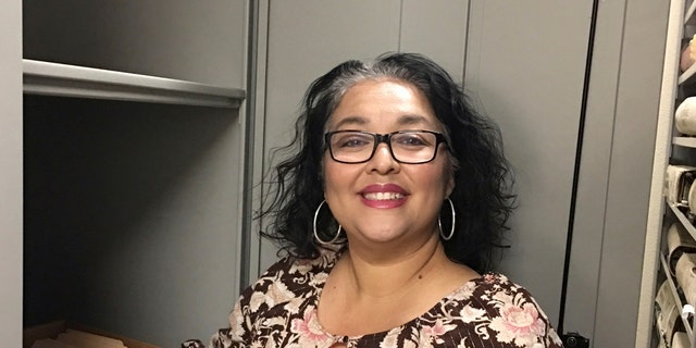 In this photo provided by the Doña Ana County Manager's Office, Records and Filing Supervisor Angelica Valenzuela poses at the Doña Ana County Clerk's Office Friday, May 19, 2017, in Las Cruces, N.M. Valenzuela found a century-old document inside a box of unarchived records that sheds light on the death of the Old West lawman Pat Garrett who gained fame for killing Billy the Kid. (Doña Ana County Manager's Office via AP)