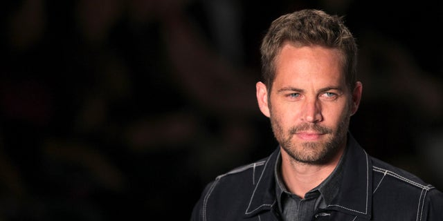 March 21, 2013. Paul Walker presents a creation from Colcci's 2013/2014 summer collection during Sao Paulo Fashion Week.
