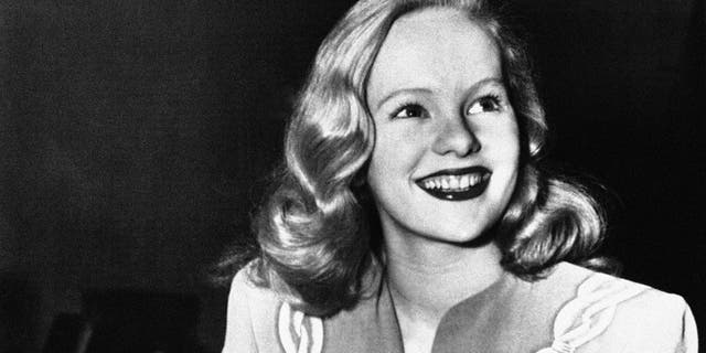 """FILE - In this Dec. 26, 1945, file photo, actress Peggy Cummins, 20, smiles in Superior Court, in Los Angeles, after her contract with Twentieth Century-Fox Studio had been approved. Cummins, who gave an indelible performance as the lethal, beret-wearing robber in the noir classic """"Gun Crazy,"""" has died. Cummins, who retired from acting in the early 1960s, died Friday, Dec. 29, 2017, in London at age 92.  (AP Photo/File)"""