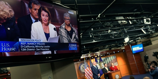 TV monitors play Pelosi's speech on the House floor while a news conference that she was scheduled to attend goes on in the background.