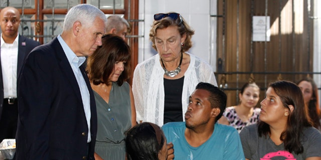 U.S. Vice President Mike Pence, left, and his wife Karen Pence, second left, meet with Venezuelans at the Calvary Chapel in Cartagena, Colombia, Monday, Aug. 14, 2017. Pence is seeking to highlight the growing plight of Venezuelans with a visit with people who've fled the country to neighboring Colombia. He prayed with faith leaders and Venezuelan families before departing to Buenos Aires, Argentina later Monday. (AP Photo/Fernando Vergara)