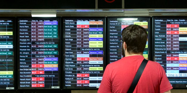 A New Jersey Transit passenger checks the schedules in New York's Penn Station, Tuesday, July 18, 2017. New Jersey Transit says some trains have been canceled this week because engineers are choosing not to work under the terms of their contract amid the summer-long repair work at Penn Station. (AP Photo/Richard Drew)