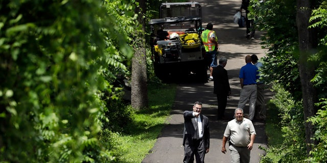 Law enforcement officials walk down a blocked off drive way, Monday, July 10, 2017, in Solebury, Pa.