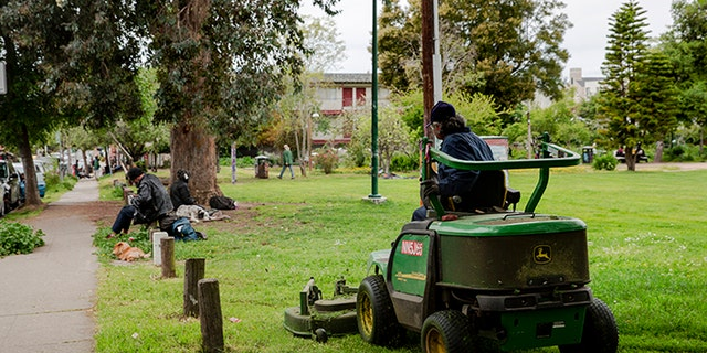 A worker mows the lawn in People's Park while a homeless man sits on the grass.