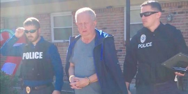 Michael Neu, shown being taken into custody, faces 269 counts of wire fraud and one count of money laundering, authorities say.