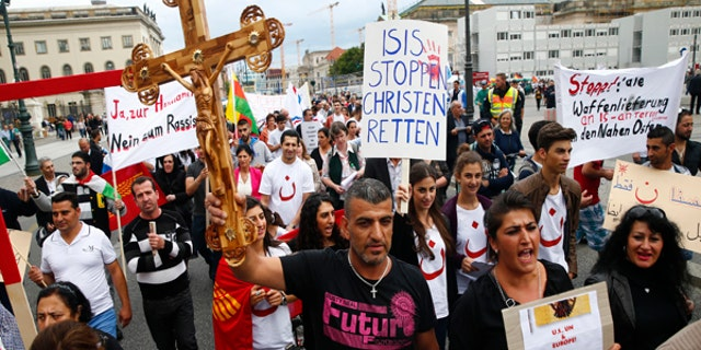 "August 17, 2014: People hold crosses and signs during a rally organized by Iraqi Christians living in Germany denouncing what they say is repression by the Islamic State militant group against Christians living in Iraq, in Berlin. Some of the signs read ""Stop ISIS, save the Christians"" and ""Stop all shipment of weapons into the Middle East."""