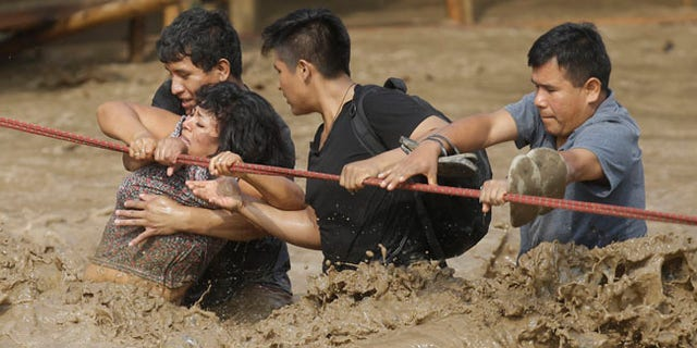 A group of people, stranded in flood waters, hold onto a rope as they wade through the water in Lima, Peru.