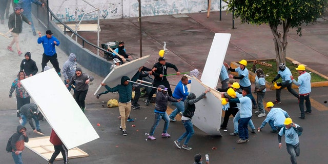 In this photo provided by the Andina government news agency, Alianza Lima club soccer fans, left, fight with members of an evangelical church, yellow helmets at right, outside the soccer club's stadium in Lima, Peru.