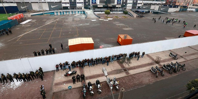 In this photo provided by the Andina government news agency, police stand guard outside the parking lot of the Alianza Lima soccer club stadium after clashes between the club's fans and members of an evangelical church in Lima, Peru.