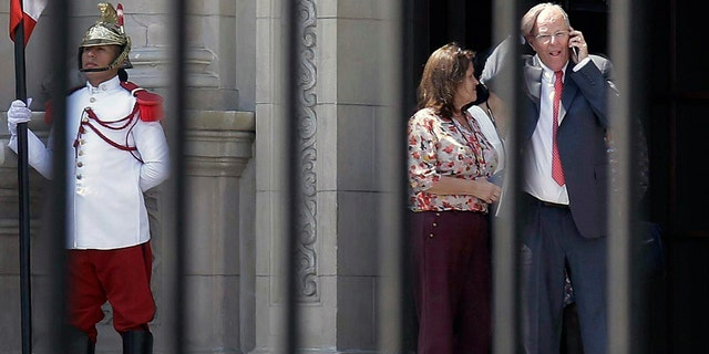 Peru's President Pedro Pablo Kuczynski talks on his cellphone as he leaves the Government Palace in Lima Wednesday.