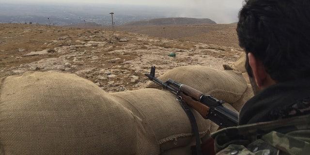 A Kurdish Peshmerga fighter takes position overlooking the town of Bashiqa, Iraq.