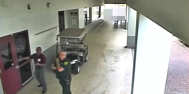 Former Deputy Scot Peterson, right, is seen on video taken during the Feb. 14 Florida school shooting.