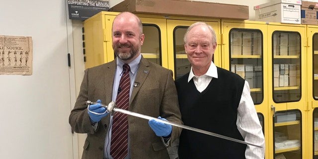 Dr. Philip Mead (left) and B. Owen Williams holding the sword (Museum of the American Revolution).