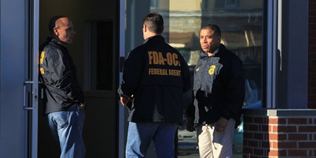 Federal agents investigate the offices of New England Compounding Center in Framingham, Mass., Tuesday, Oct. 16, 2012. The company's steroid medication has been linked to a deadly meningitis outbreak. FDA spokesman Steven Immergut says the visit is part of the investigation into the outbreak, which has killed at least 15 people and sickened more than 200 others in 15 states. (AP Photo/The Boston Globe, Barry Chin)  BOSTON HERALD OUT, QUINCY OUT