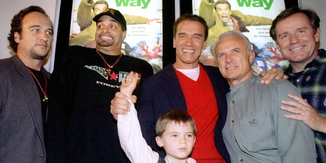 """Actor Arnold Schwarzenegger, red sweater, is flanked by co-stars, from left, James Belushi, Sinbad, Robert Conrad and Phil Hartman and holds the hand of Jake Lloyd, before attending the premiere of their film, """"Jingle All The Way, at the Mall of America in Bloomington, MN, November 16, 1996."""