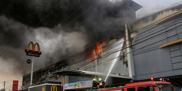 Firemen battle a fire that rages at a shopping mall, Saturday, Dec. 23, 2017, in Davao city, southern Philippines.