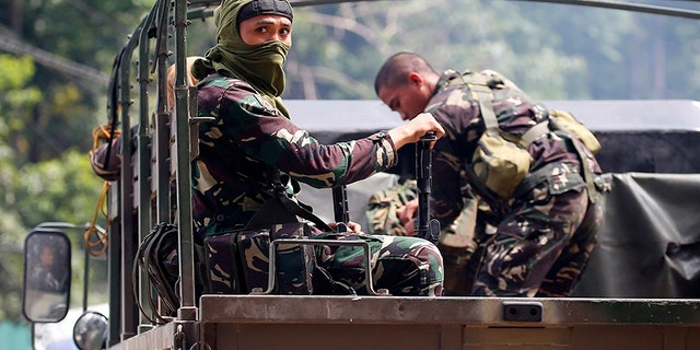 Government troops head for a continuing military operation against Muslim militants who lay siege in Marawi city Friday, May 26, 2017 at Bal-oi township, Lanao del Norte province in southern Philippines. Philippine army generals say dozens of Islamic State group-linked extremists have been killed in two days of fighting in a southern city that has been under siege since one of Asia's most-wanted militants evaded capture and dozens of rebels came to his aid. (AP Photo/Bullit Marquez)
