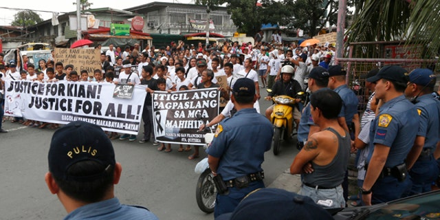 Police officers watch as protesters and supporters march with the hearse of carrying the body of Kian Loyd delos Santos, a 17-year-old student, during his funeral Saturday, Aug.26, 2017, in suburban Caloocan city north of Manila, Philippines. Murder complaints were filed Friday against Philippine police officers in connection with the killing of a teenager that has sparked an outcry against the president's anti-drug crackdown, which has left thousands dead.