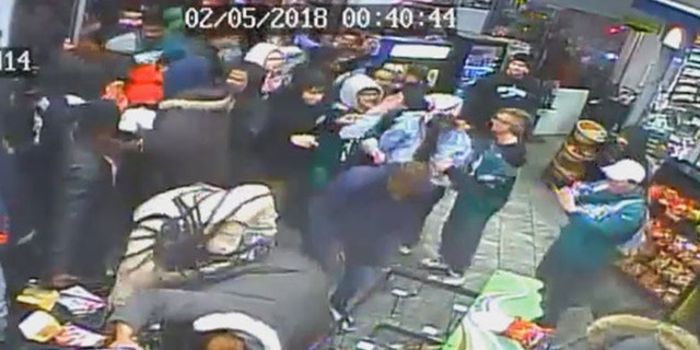 Security camera shows people throwing food items and soft drinks on the floor and at walls of a South Philadelphia gas station.