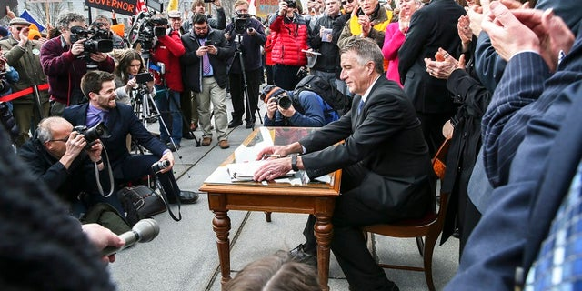 Gov. Phil Scott, in April, signing gun control legislation that drew fierce protests.