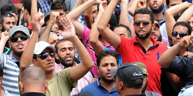 Tunisian protestors shout slogans outside the courthouse where Amina Sboui, the Tunisian member of the Ukrainian feminist group Femen, is being put on trial in Kairouan on May 30, 2013. Three European activists with the women's topless protest group Femen, jailed for four months for baring their breasts in Tunis, will appeal their sentence.