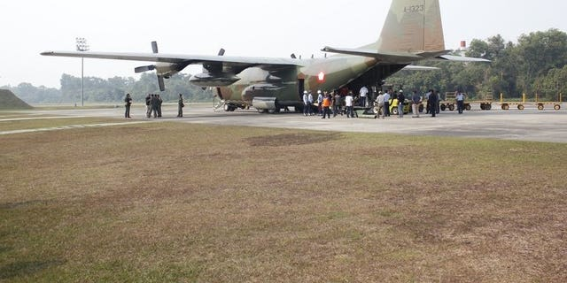Soldiers and government personnel unload sacks of salt from an Indonesian Air Force Hercules, in Sumatra, on June 22, 2013. It was in preparation for a mission seeding clouds in an attempt to create rain to extinguish raging fires that have cloaked neighbouring Singapore and Malaysia in choking smog.