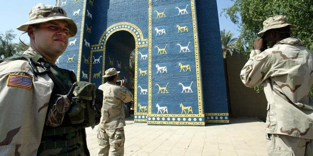 US soldiers take pictures of the Ishtar Gate in the ancient city of Babylon, on September 28, 2003. At ancient Babylon's Ishtar Gate -- workers labour with a heavy saw, hammers, a chisel and crowbar to break up and remove a concrete slab that is hastening the structure's decay.