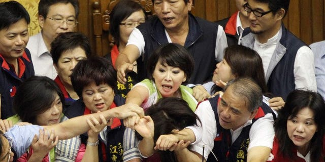 Legislators from Taiwan's ruling Kuomintang party and opposition try to seize the podium in parliament on June 25, 2013. Fighting broke out in Taiwan's parliament Tuesday as legislators scuffled and threw coffee during a debate on whether a controversial capital gains tax on share trading should be revised less than a year after it was brought in.