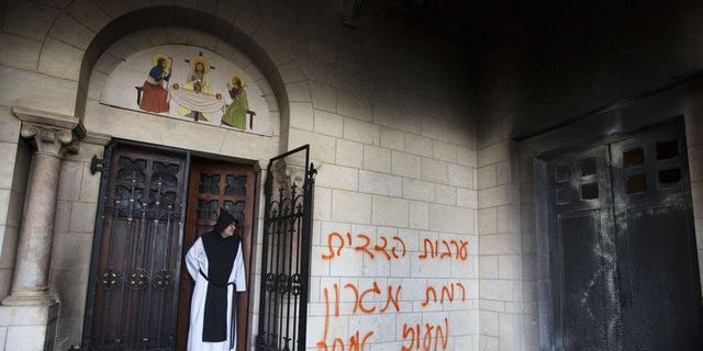 A picture taken on September 4, 2012 shows a Trappist monk looking at graffiti which was sprayed on the wall of the Latrun monastery. A court has extended the remand of an Israeli man arrested on suspicion of vandalising the Catholic monastery in an attack that shocked the Holy Land's religious and political establishment.