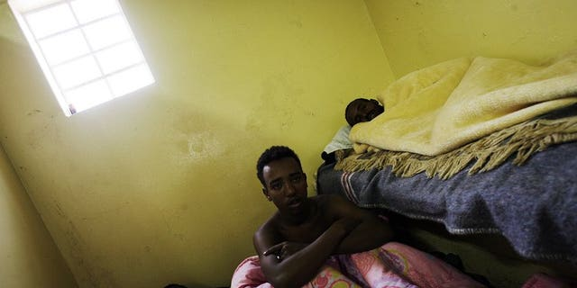 Sick Somali foreign nationals lay cramped in a toilet at a temporary refugee camp in Soetwater on the outskirt of Cape Town on June 18, 2008. A Somali envoy on Tuesday met officials in Pretoria in a bid to ease tensions stirred by recurring attacks on Somali refugees in South Africa.