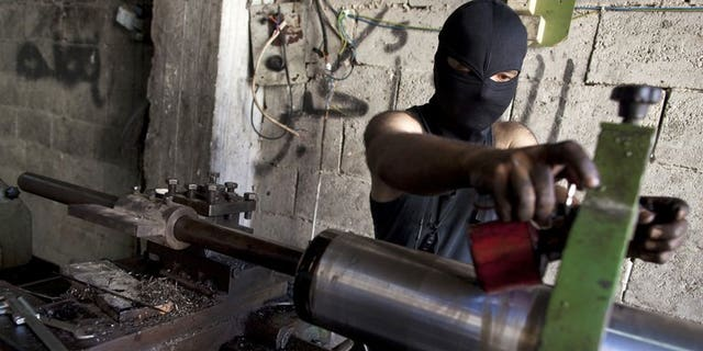 A man assembles an improvised cannon to be used by rebel fighters, at a factory in Syria's Aleppo city, on July 7, 2013. Islamic extremists fighting in Syria pose one of the most worrying threats to Britain and its allies, particularly if they gain access to the regime's stocks of chemical weapons, parliament's intelligence committee says.