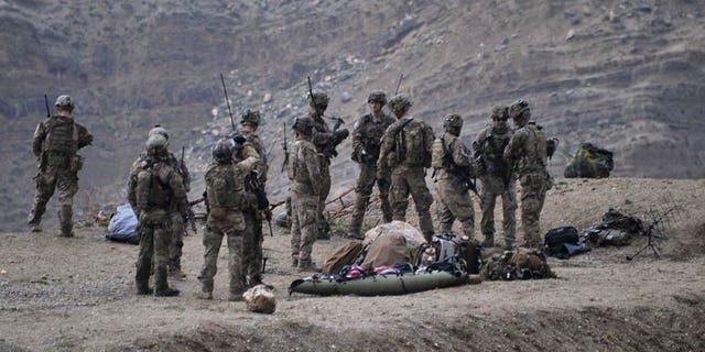 US soldiers gather near the scene of a helicopter crash in Afghanistan's Nangarhar province on April 9, 2013.