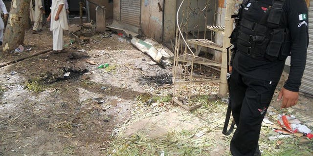 A Pakistani policeman stands at the site of a motorcycle bomb explosion in the northwestern province of Khyber Pakhtunkhwa, on July 11, 2013. At least two people were killed and five others wounded when a motorcycle bomb exploded at a roadside restaurant in northwest Pakistan.