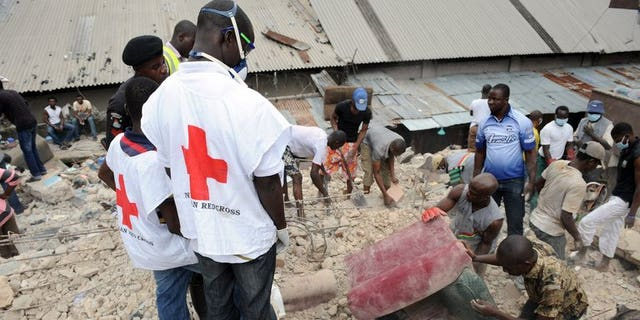 Red Cross officials help with rescue work after a building collapses at Idumota in Lagos in July 2011. A pregnant woman and a baby were among seven people killed after a residential building collapsed in Nigeria's most crowded city, Lagos, on Thursday.
