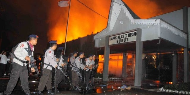 Indonesian policemen secure the entrance of a burning prison compound in Medan city on July 11, 2013. At least five people have been killed in violent riots at the jail and about 100 prisoners, including terror convicts, are still on the loose, police said Friday.