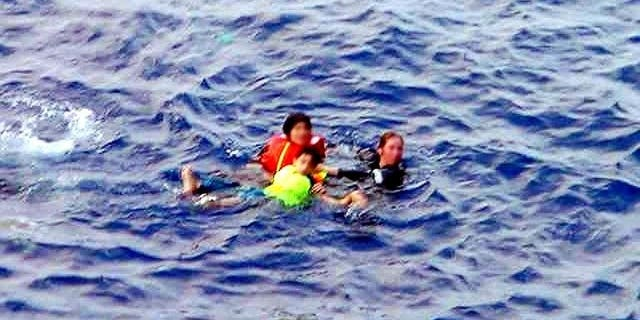In this file photo, an Australian Navy officer (R) rescues two refugee children from the sea off Christmas Island, on October 10, 2001. The rescue authorities on Sunday said a search for eight people missing after a boat carrying 97 asylum-seekers sank in remote seas had ended, with little chance anyone would be found alive.