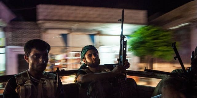 """Syrian rebels head to the town of Bsankol in the northwestern province of Idlib on July 11, 2013. Britain is to give Syrian opposition fighters equipment to protect them against chemical weapons attacks """"as a matter of special urgency"""", Foreign Secretary William Hague said."""