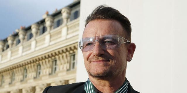 Bono, lead singer of Irish rock band, U2, poses after receiving the Commander of the Order of Arts and Letters (Commandeur de l'ordre des Arts et des lettres) insignia on July 16, 2013 in Paris.