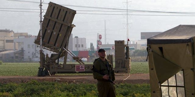 """An Israeli soldier stands in front of an """"Iron Dome"""" short-range missile defence system near the northern Israeli city of Haifa on May 6, 2013. Israel deployed its Iron Dome missile defence system near the Red Sea resort of Eilat, which is close to the border with Egypt, an army spokeswoman said."""