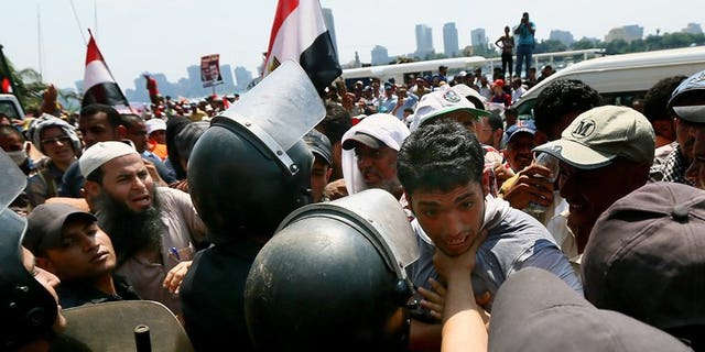 A supporter of Egypt's ousted president Mohamed Morsi is held back by riot police during a rally in Cairo on July 17, 2013. Britain has announced it is revoking export licences for equipment used by Egypt's military and police amid concerns it could be used against protesters.