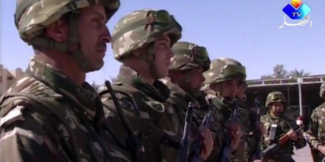 An image grab taken from footage provided by Algeria's Ennahar TV on January 18, 2013 and filmed in June 2012 shows Algerian soldiers standing to attention in the desert at an undisclosed location in the south of the country. Algerian soldiers shot dead four Islamists during an overnight raid in the town of Sour El-Ghozlane southeast of the capital Algiers, security sources said.