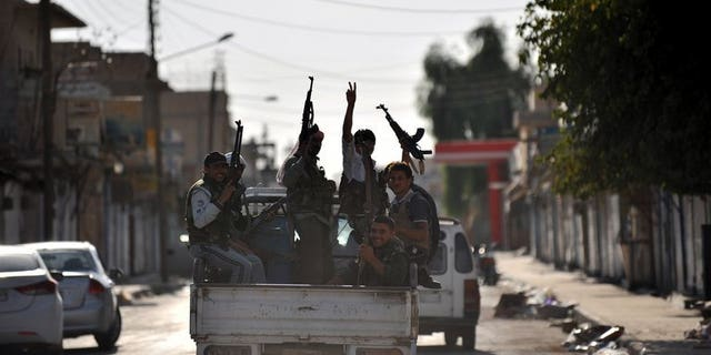 Syrian rebels raise their weapons during a patrol in the town of Tal Abyad near the border with Turkey on October 5, 2012. Syrian Kurdish fighters in the north fought fierce battles against jihadists and captured a commander of the Islamic State of Iraq and the Levant (ISIS) late Saturday, a monitoring group said.