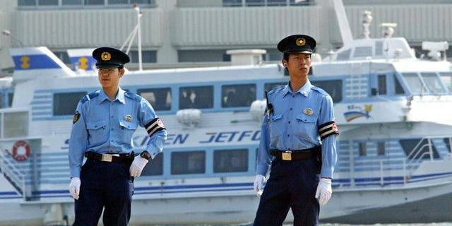 """Japanese policemen patrol the Niigata Port, on June 8, 2003. Police on Friday arrested a man who left a """"haiku"""" poem when he disappeared after five people were murdered in a tiny mountain village."""