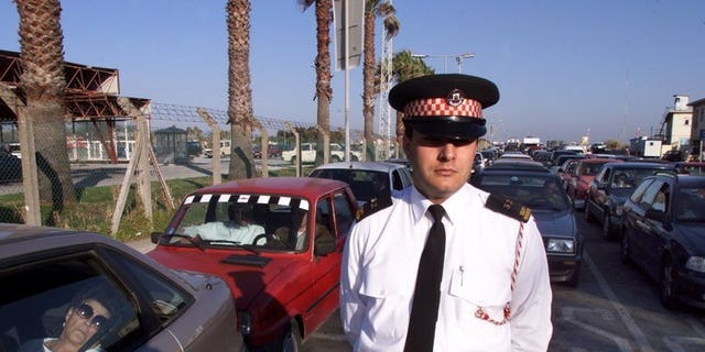 """File picture shows a policeman monitoring traffic as cars wait to cross from Gibraltar into Spain. The government said Sunday it had """"serious concerns"""" after Gibraltar accused Madrid of deliberately creating delays to car traffic to and from the disputed British-held territory to Spain."""