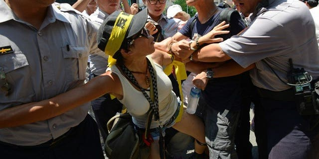 """Police clash with protesters opposing trade between Taiwan and China outside parliament in Taipei on July 30, 2013. Chanting """"Opposing the trade service agreement, safeguarding sovereignty"""", demonstrators attempted to push their way through a police cordon around parliament in Taipei."""