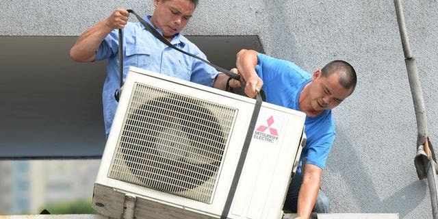 Workers install an air-conditioning unit at a food stall in Shanghai on July 2, 2013. More than 10 people have died in China's commercial hub Shanghai, a local health official said Wednesday as the city grapples with its highest temperatures in at least 140 years.