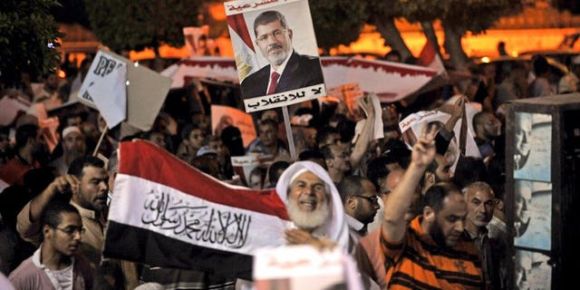 """Egyptian supporters of Mohamed Morsi hold his portrait during a demonstration against the government in Cairo, on July 31, 2013. Egypt's cabinet have tasked police to take """"necessary measures"""" to end protests by supporters of ousted president Mohamed Morsi, terming them a national security threat."""