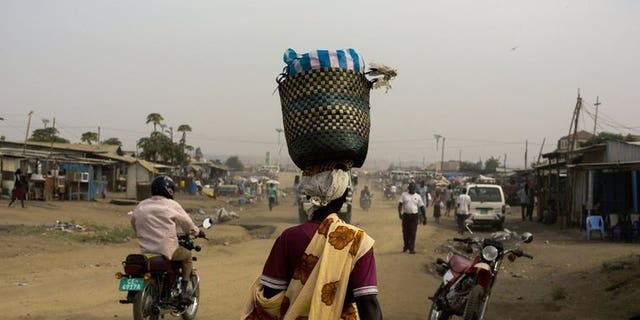 A woman walks through Gudele market in Juba, South Sudan. Two Ugandan journalists were freed in South Sudan on Wednesday after four nights in detention for filming in the capital Juba, the reporters said.